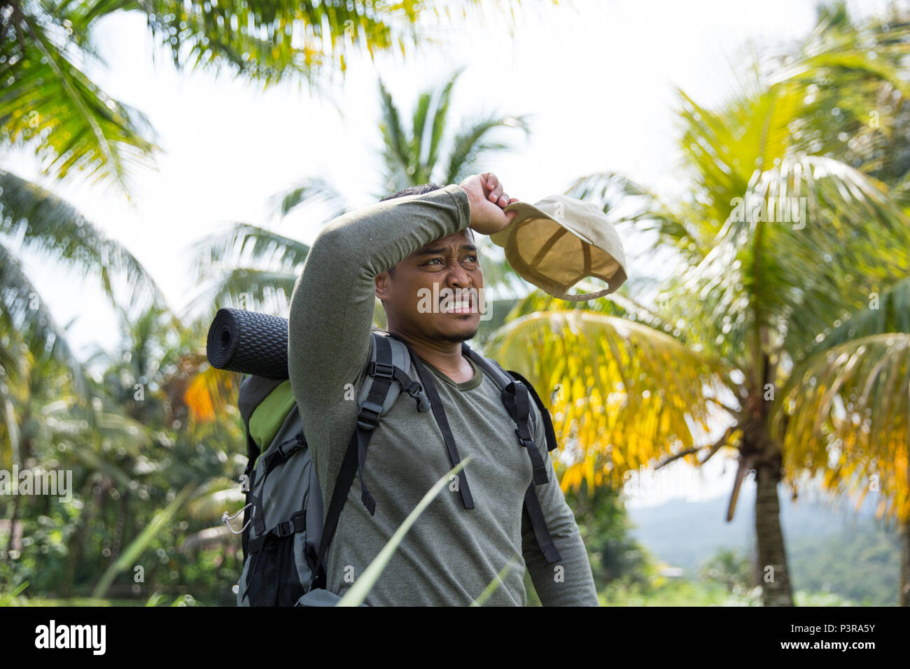 asian hiker wipe his forehead - Stock Image