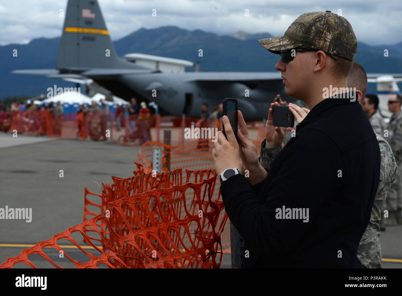 Gregory Decker, a weapons systems coordinator with 3rd Maintenance Group at JBER takes photos of the U.S. Navy Flight Demonstration Squadron, the Blue Angels take-off during Arctic Thunder Special Needs and Family Day, July 29, 2016. JBER will open the doors to the public, showcasing more than 40 key performers and ground acts to include the JBER joint forces, U.S. Air Force F-22, and U.S. Navy Blue Angels demonstrations teams. (U.S Air Force photo by Airman 1st Class Javier Alvarez) Stock Photo