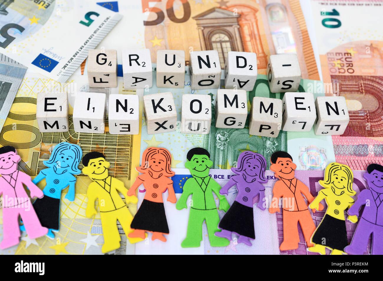 Letter cube forms the word basic income on money, Buchstabenwürfel formen das Wort Grundeinkommen auf Geldscheinen - Stock Image