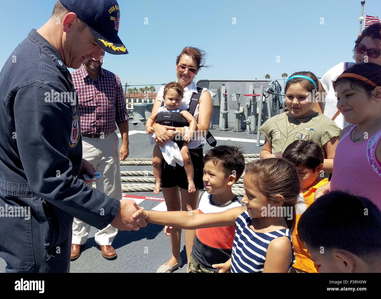 Naval Information Forces West provided a tour of the Naval Base San Diego to local students and their parents July 22.  The families belong to the Marlow B. Martinez Foundation, a local non-profit organization supporting disadvantaged children. Cmdr Patrick H. O'Mahoney the Commanding Officer of the USS Sampson DDG-102 took time to meet with the kids and pass out stickers. (US Navy photo by LCDR Henry A. Martinez / released) - Stock Image
