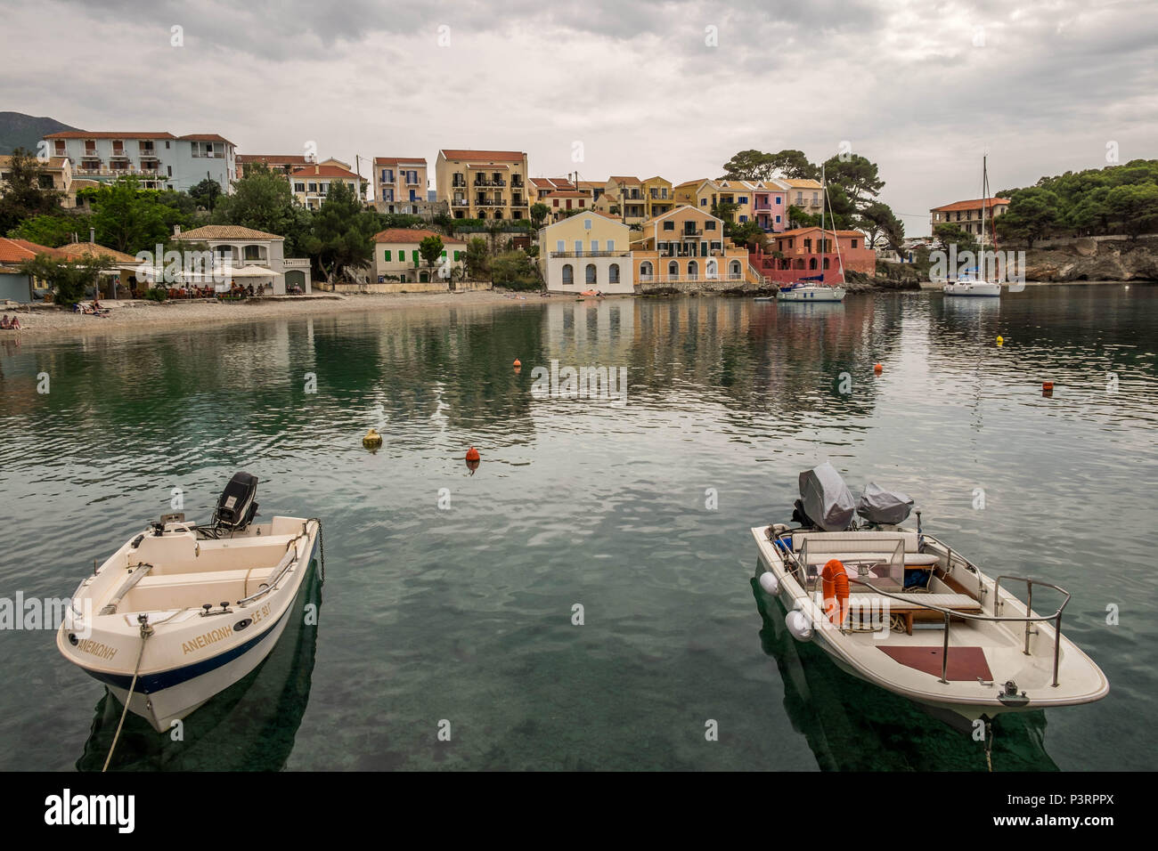Assos beach showing small boats and crane for lifting boats out of the water. - Stock Image