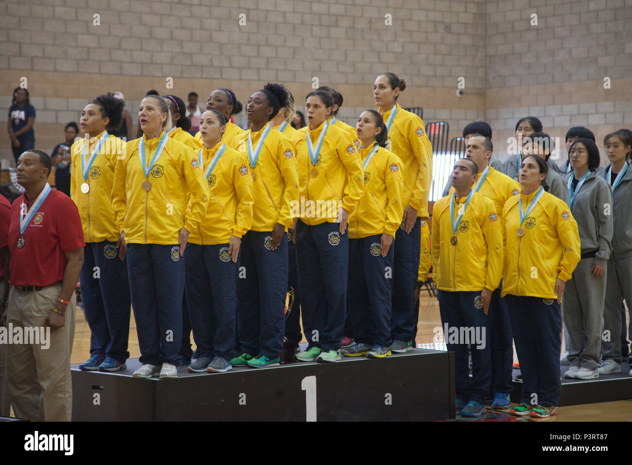 The team representing the Brazil in the World Military Women's Basketball Championship, stand at attention and sing their National Anthem during the 2016 Conseil International Du Sport Militaire (CISM) awards ceremony on Camp Pendleton, Calif., July 29, 2016. The CISM championships are hosted around the world and provide an avenue for the United States to project the positive image with valuable military-to-military engagement through sports. (U.S. Marine Corps photo by Cpl. Tyler S. Dietrich) - Stock Image