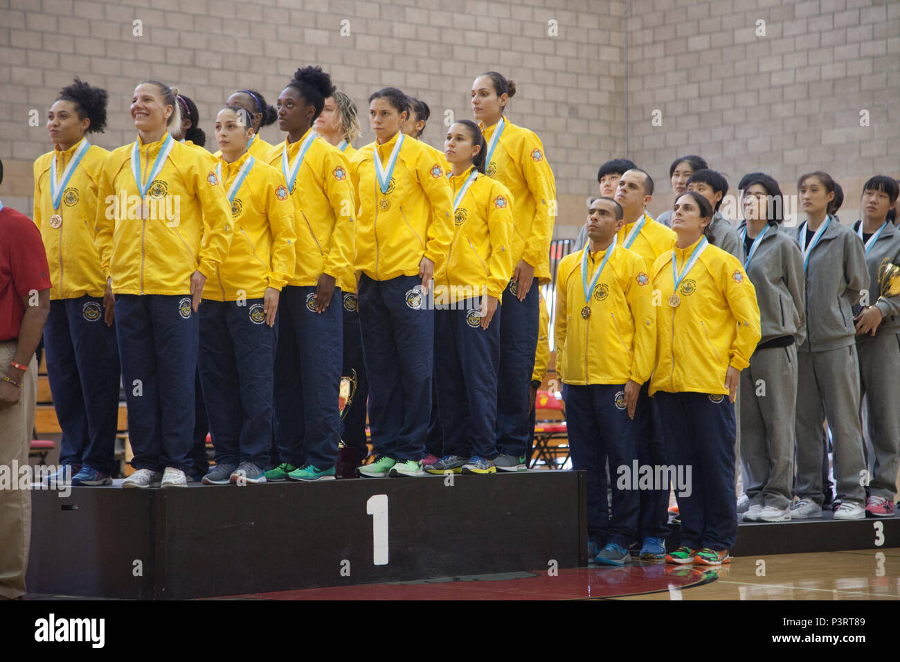 The team representing the Brazil in the World Military Women's Basketball Championship, stand at attention for the playing of their National Anthem during the 2016 Conseil International Du Sport Militaire (CISM) awards ceremony on Camp Pendleton, Calif., July 29, 2016. The CISM championships are hosted around the world and provide an avenue for the United States to project the positive image with valuable military-to-military engagement through sports. (U.S. Marine Corps photo by Cpl. Tyler S. Dietrich) - Stock Image