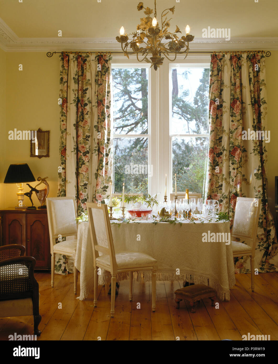 White Upholstered Chairs And Table With White Cloth In Front Of Window With Floral Curtains In Country Dining Room Stock Photo Alamy