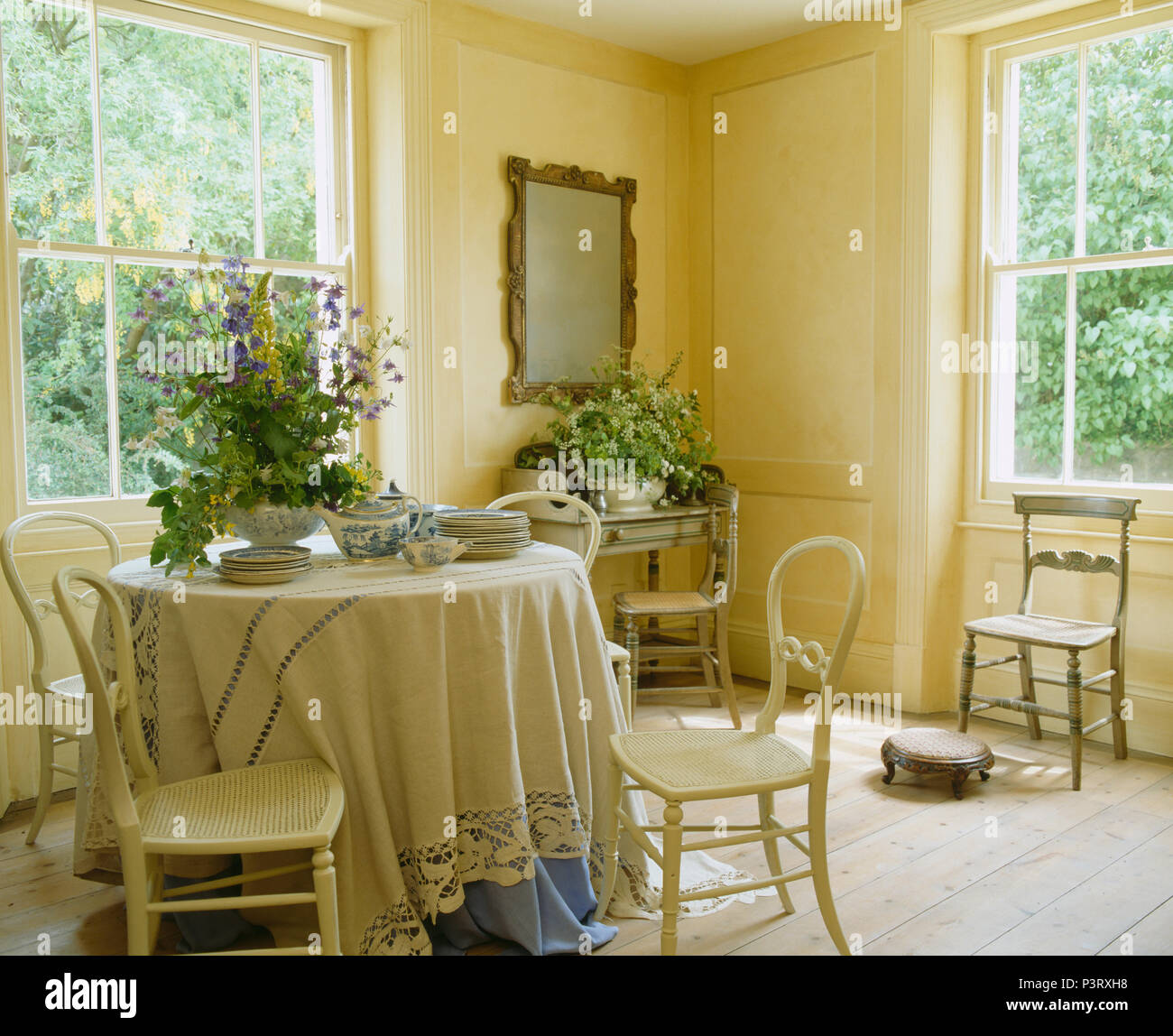 Cream painted antique chairs at circular table with cream cloth in elegant  cream dining room with wooden flooring - Cream Painted Antique Chairs At Circular Table With Cream Cloth In