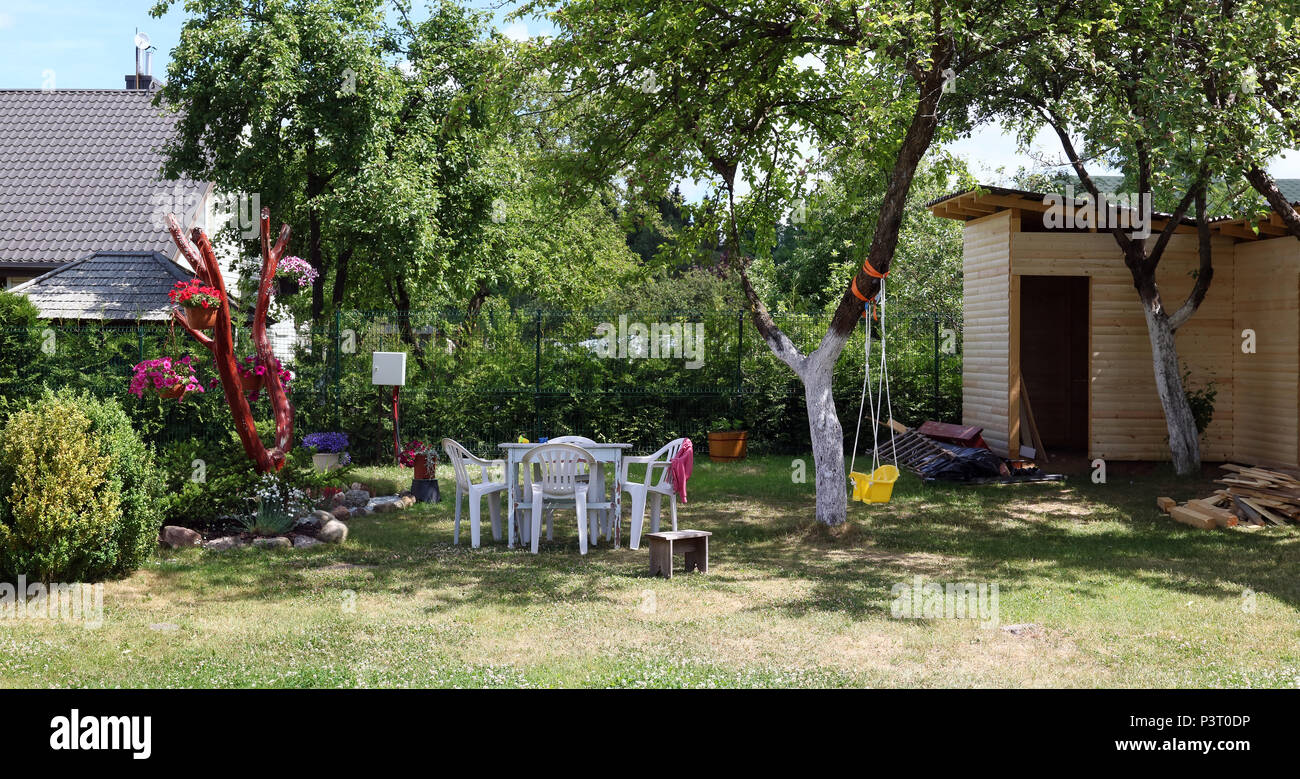 Backyard of an ordinary poor village house-- plastic furniture, a swing and an unfinished barn. Sunny summer day panoramic landscape - Stock Image