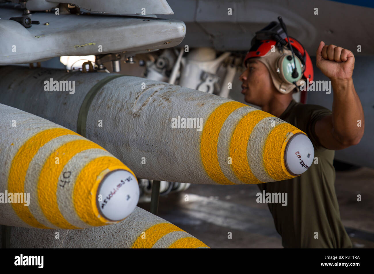 Cpl. Javon Franklin, an aviation ordnance technician with Marine Fighter Attack Squadron (VMFA) 122, assists in loading high explosive ordnance on an F/A-18C Hornet during exercise Southern Frontier at Royal Australian Air Force Base Tindal, Australia, July 28, 2016. Southern Frontier is three weeks of unit level training helping the squadron gain experience and qualifications in low altitude, air-ground, high explosive ordnance delivery at the unit level. VMFA-122 is home based out of Marine Corps Air Station Beaufort, South Carolina and are currently assigned to MAG-12 at MCAS Iwakuni under  - Stock Image