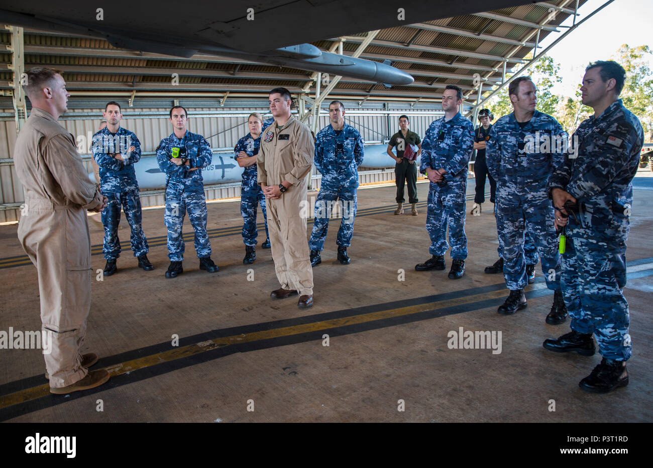 U.S Marine Corps Cpl. Jesse Meyers, a power liner with Marine Fighter Attack Squadron (VMFA) 122, gives a familiarization class to Cpl. Michael Barton, an aircraft rescue firefighter specialist with Marine Wing Support Squadron (MWSS) 171, and the No. 17 Squadron Fire and Rescue team at Royal Australian Air Force Base Tindal, Australia, July 28, 2016. Barton is a liaison between VMFA-122 and No. 17 Squadron firefighters in case of emergencies involving the flying squadron's aircraft during Exercise Pitch Black 2016. The familiarization class covered the basic dos and don'ts of operating around - Stock Image