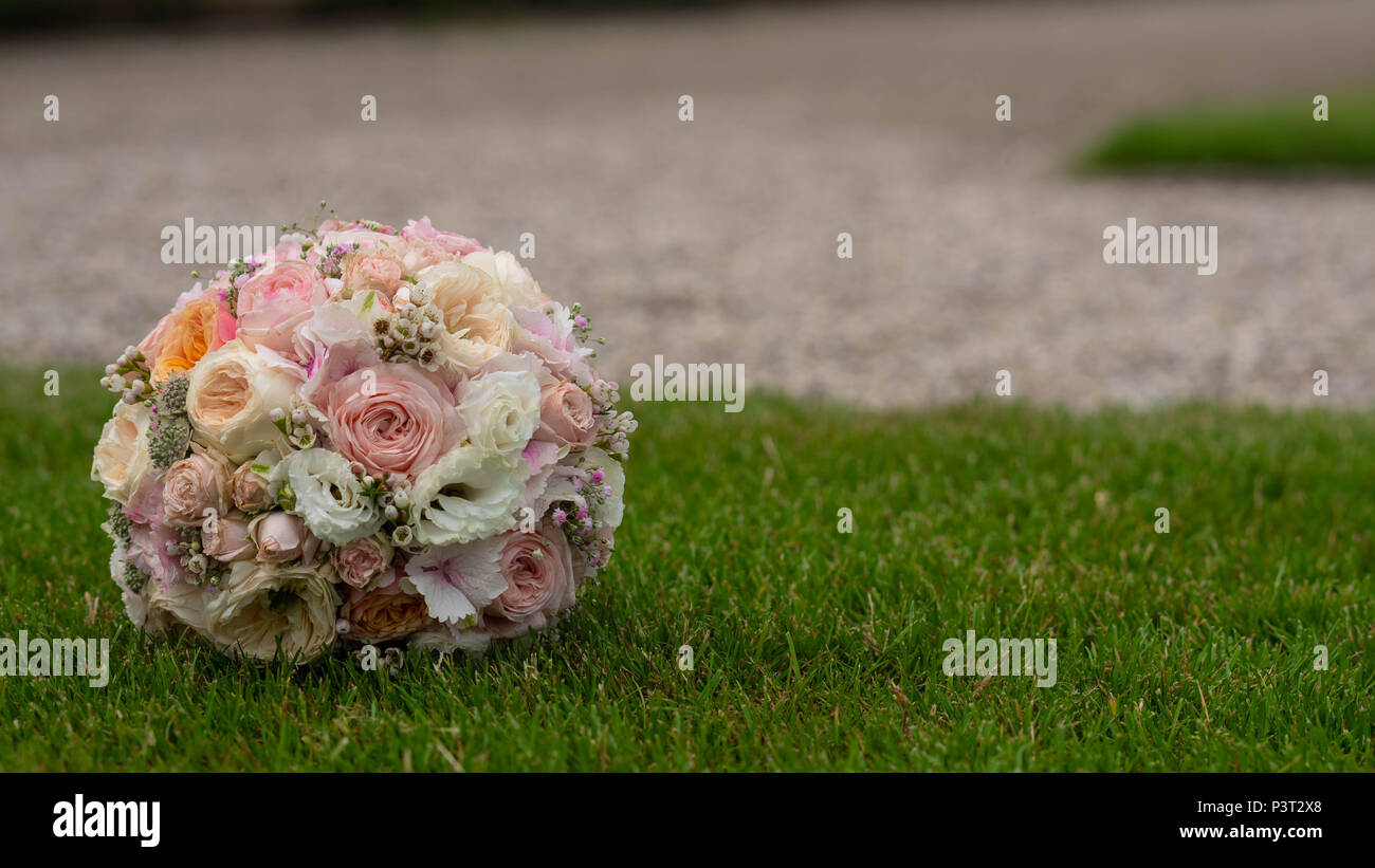 Closeup view of one big round beautiful fresh wedding bouquet of closeup view of one big round beautiful fresh wedding bouquet of rose flowers pink white and yellow pastel colors lying on green grass sunny day outdo izmirmasajfo