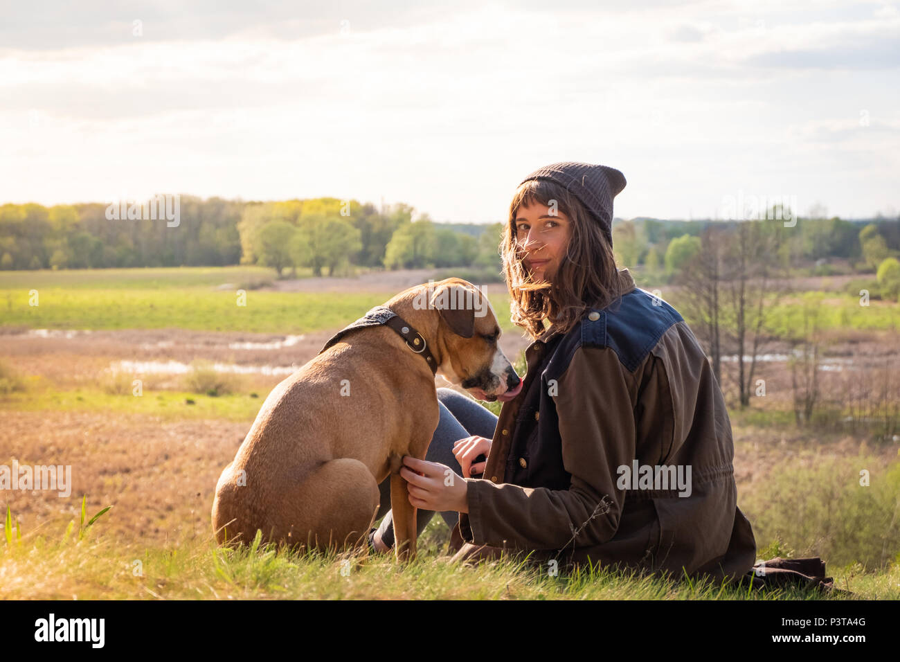 Beautiful hiking girl sit on hill with pet dog at walk. Young female person together with staffordshire terrier at meadow on warm sunny afternoon - Stock Image