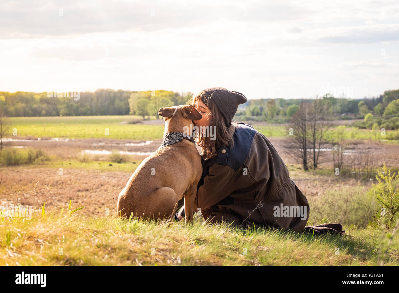 Beautiful hiking girl sit on hill and kiss pet dog at walk. Young female person together with staffordshire terrier at meadow on warm sunny afternoon - Stock Image