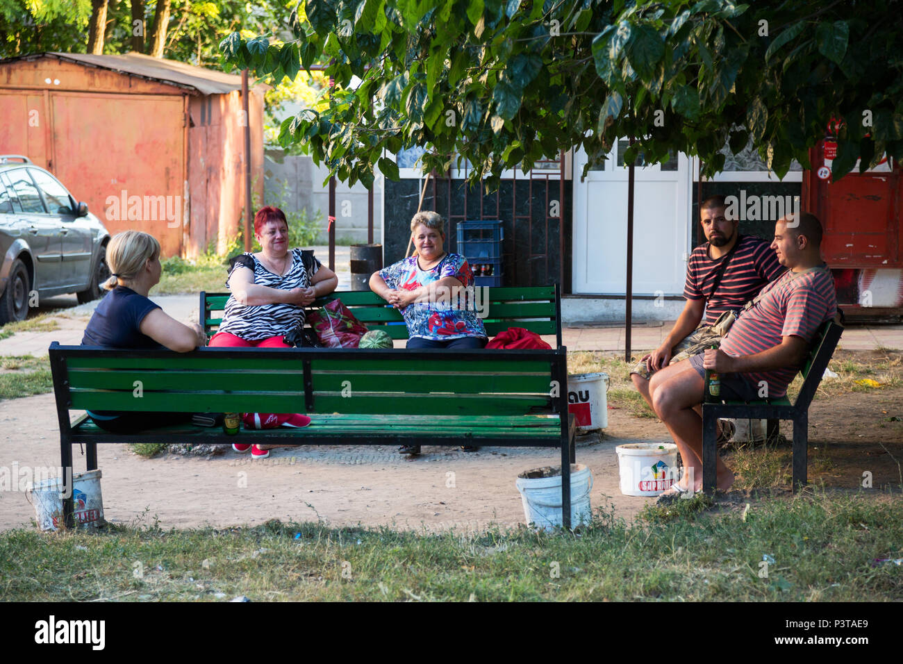 Republic of Moldova, Chisinau - Neighbors sit together on benches after work - Stock Image