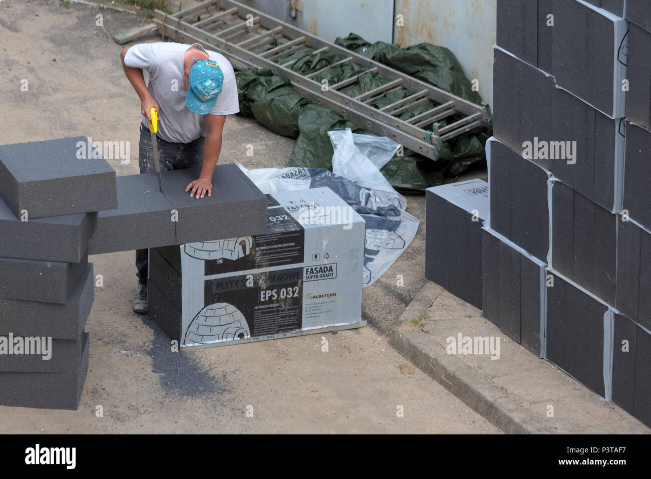 Poland - construction worker is cutting styrofoam for a thermal damaging measure on an old building - Stock Image