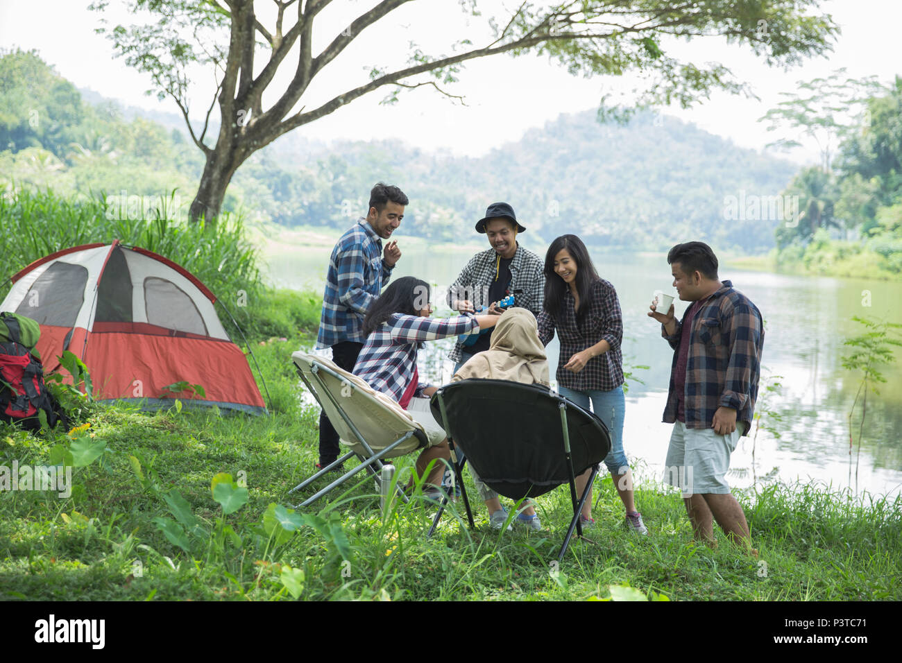 Friends Relaxing Outside Tents On Camping - Stock Image