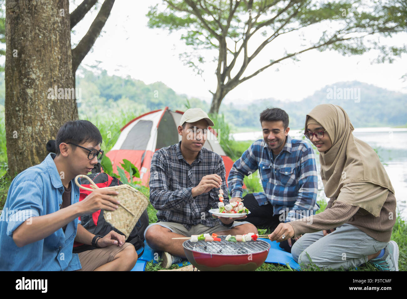 Friends making a barbecue together outdoors - Stock Image