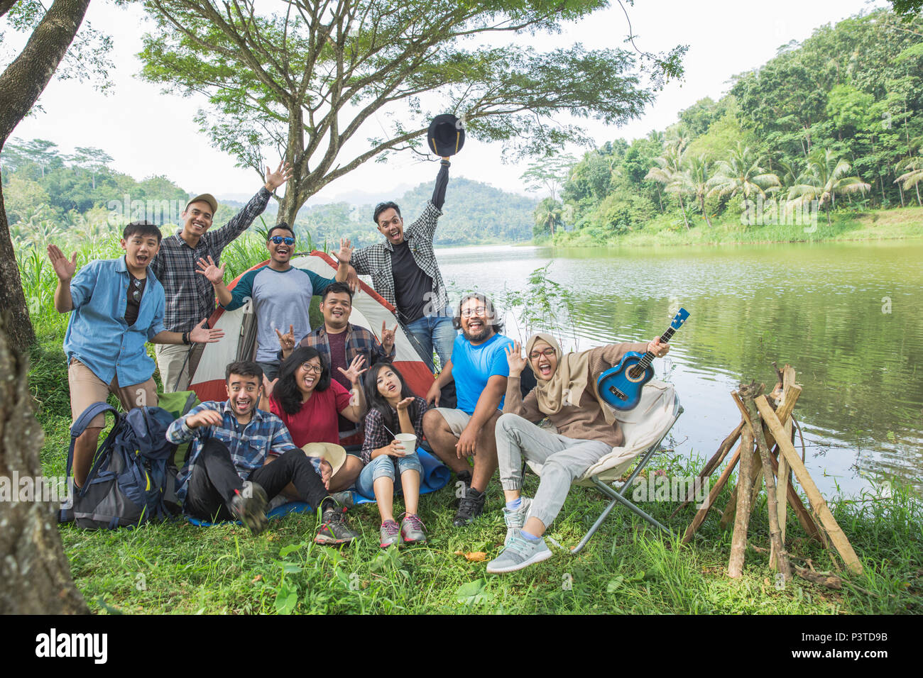 people enjoying their holiday camping together - Stock Image
