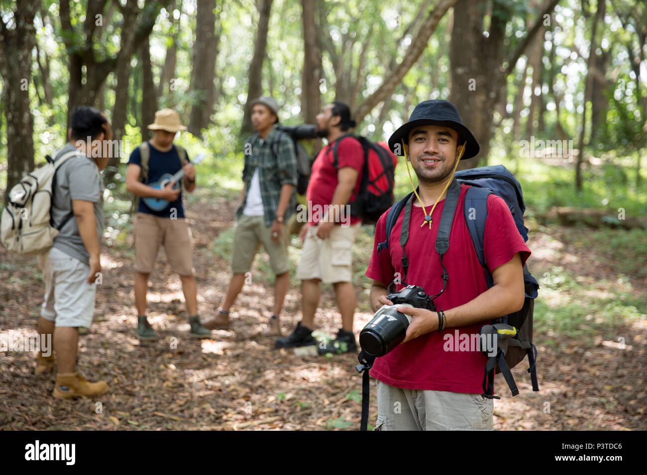 hiker with backpack holding camera - Stock Image