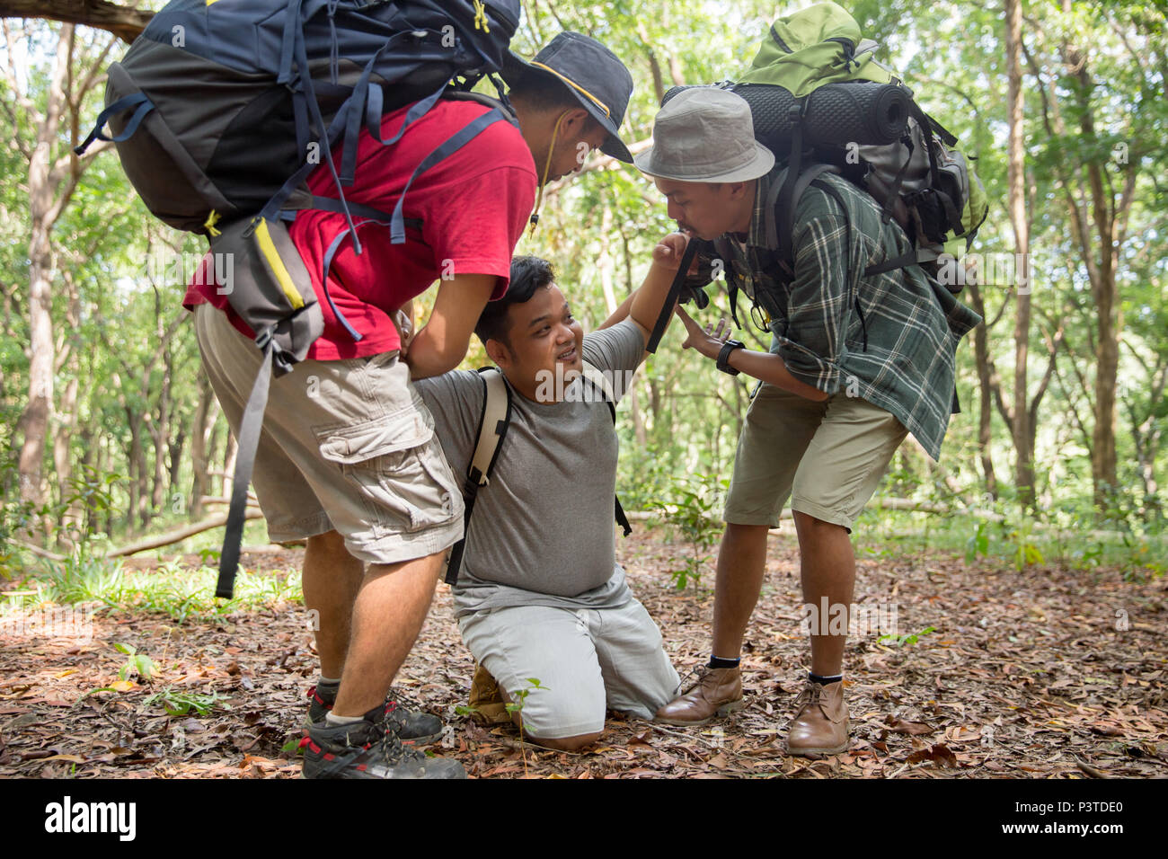 man need help to get up while hiking - Stock Image