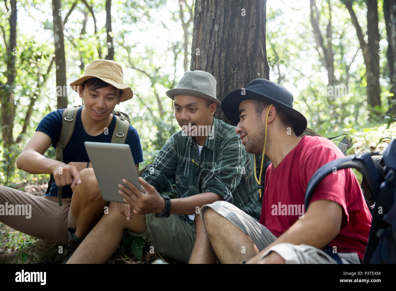 three people using tablet pc together - Stock Image