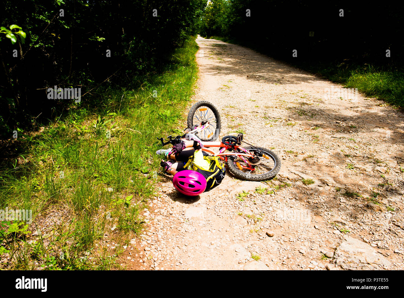 Little girl falling off her bicycle - Stock Image