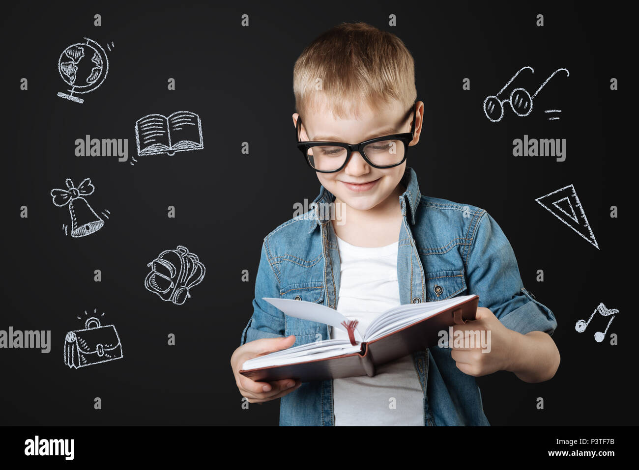 Smiling schoolboy wearing glasses while reading - Stock Image