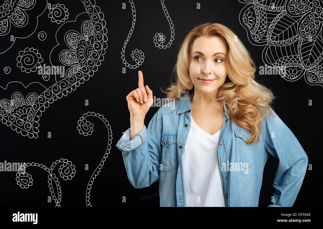 Cheerful housewife pointing her finger up and smiling - Stock Image