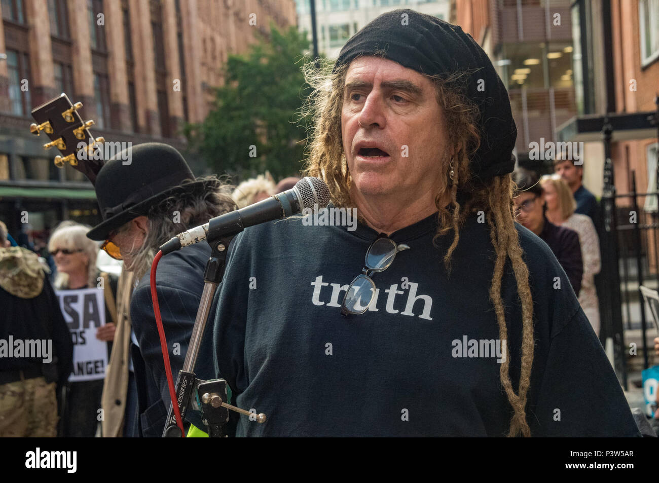 London, UK. 19th June 2018. Ciaron O'Reilly introduces the speakers and singers at the rally outside the Ecuadorian Embassy in London calling for Julian Assange to be allowed safe passage to the place of his choice to mark six years since he was given asylum there. They called for the UK authorities to allow him to leave the embassy and go to the country of his choice without being arrested. Credit: Peter Marshall/Alamy Live News - Stock Image