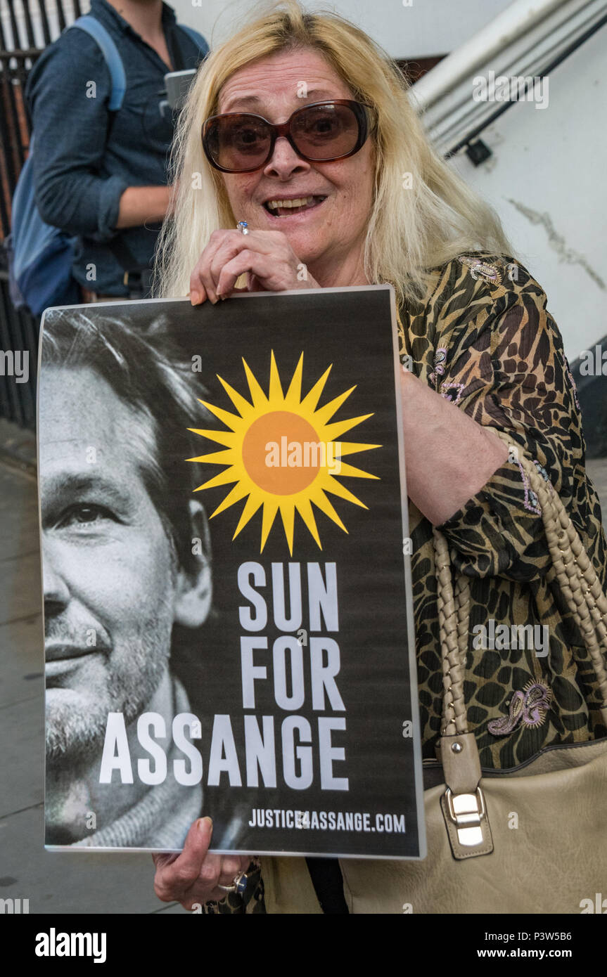 London, UK. 19th June 2018. A woman holds a poster 'Sun For Assange'  at the rally outside the Ecuadorian Embassy in London calling for Julian Assange to be allowed safe passage to the place of his choice to mark six years since he was given asylum there. His health is suffereing from being in a small space with little or no sunlight or exercise. They called for the UK authorities to allow him to leave the embassy and go to the country of his choice without being arrested. Credit: Peter Marshall/Alamy Live News - Stock Image