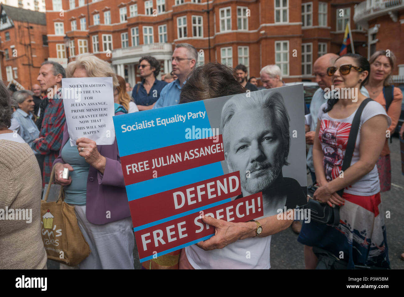 London, UK. 19th June 2018. People with posters at the rally outside the Ecuadorian Embassy in London calling for Julian Assange to be allowed safe passage to the place of his choice to mark six years since he was given asylum there. They called for the UK authorities to allow him to leave the embassy and go to the country of his choice without being arrested. Credit: Peter Marshall/Alamy Live News - Stock Image