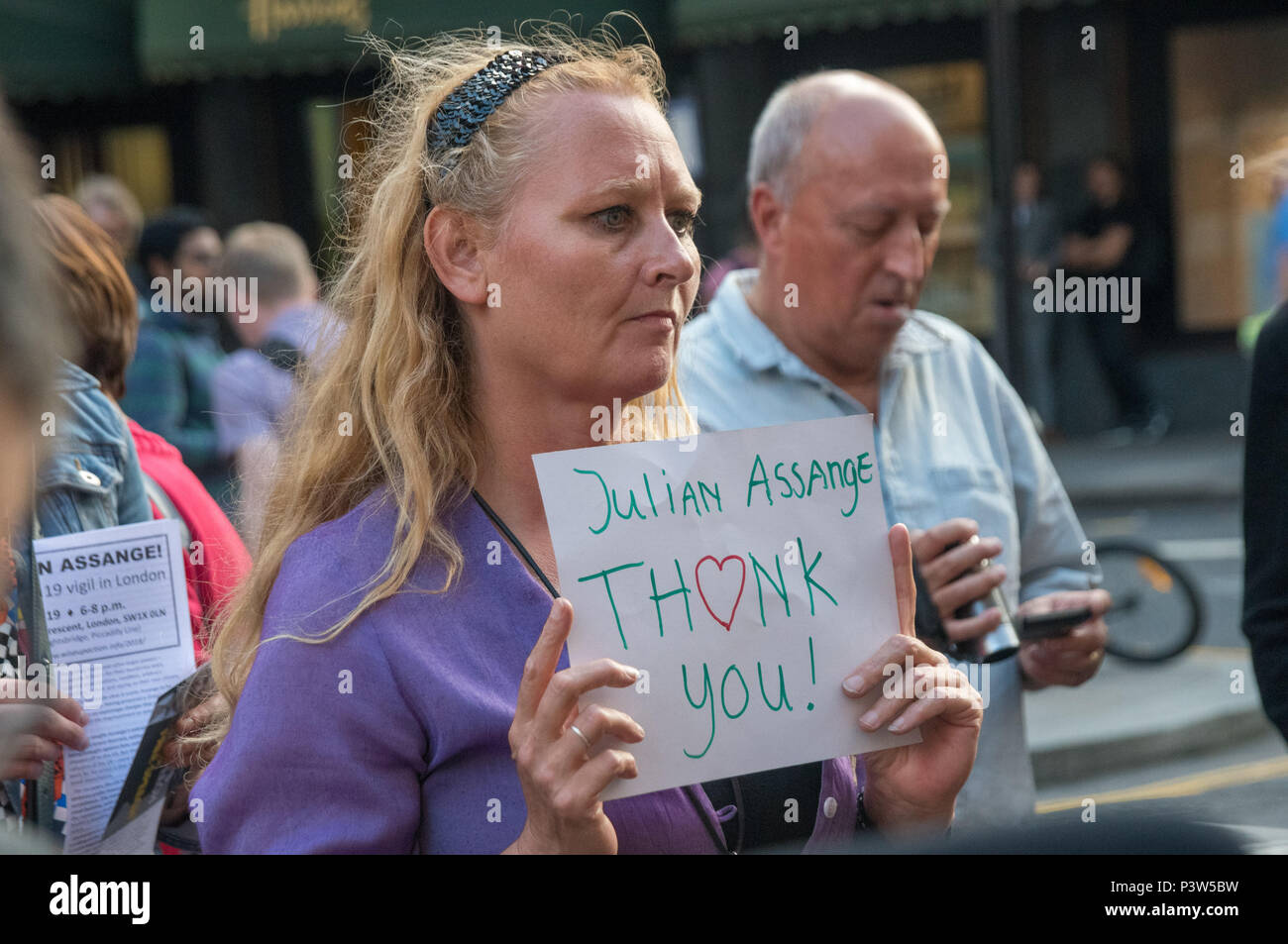 London, UK. 19th June 2018. A woman holds a small poster 'Julian Assange Thank you !' at the rally outside the Ecuadorian Embassy in London calling for Julian Assange to be allowed safe passage to the place of his choice to mark six years since he was given asylum there. They called for the UK authorities to allow him to leave the embassy and go to the country of his choice without being arrested. Credit: Peter Marshall/Alamy Live News - Stock Image