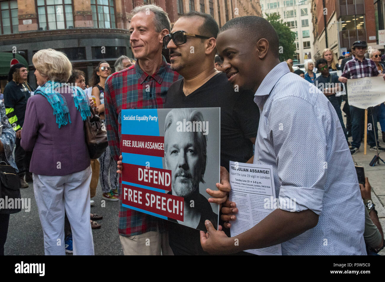 London, UK. 19th June 2018. Peter Tatchell poses for a photograph with others at the rally outside the Ecuadorian Embassy in London calling for Julian Assange to be allowed safe passage to the place of his choice to mark six years since he was given asylum there. They called for the UK authorities to allow him to leave the embassy and go to the country of his choice without being arrested. Credit: Peter Marshall/Alamy Live News - Stock Image