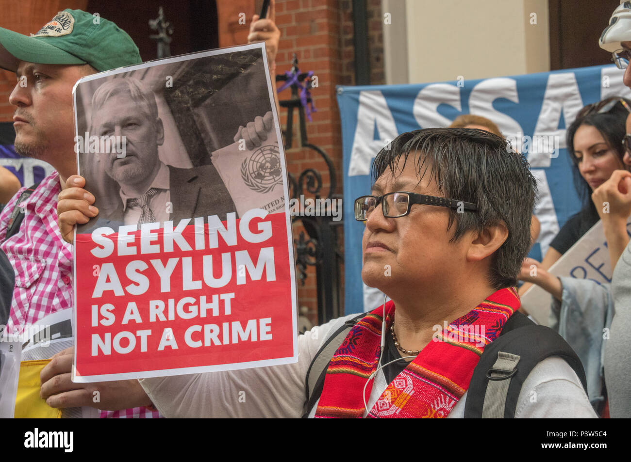London, UK. 19th June 2018. A woman holds up a poster 'Seeking Asylum is a right not a crime' at the rally outside the Ecuadorian Embassy in London calling for Julian Assange to be allowed safe passage to the place of his choice to mark six years since he was given asylum there. They called for the UK authorities to allow him to leave the embassy and go to the country of his choice without being arrested. Credit: Peter Marshall/Alamy Live News - Stock Image