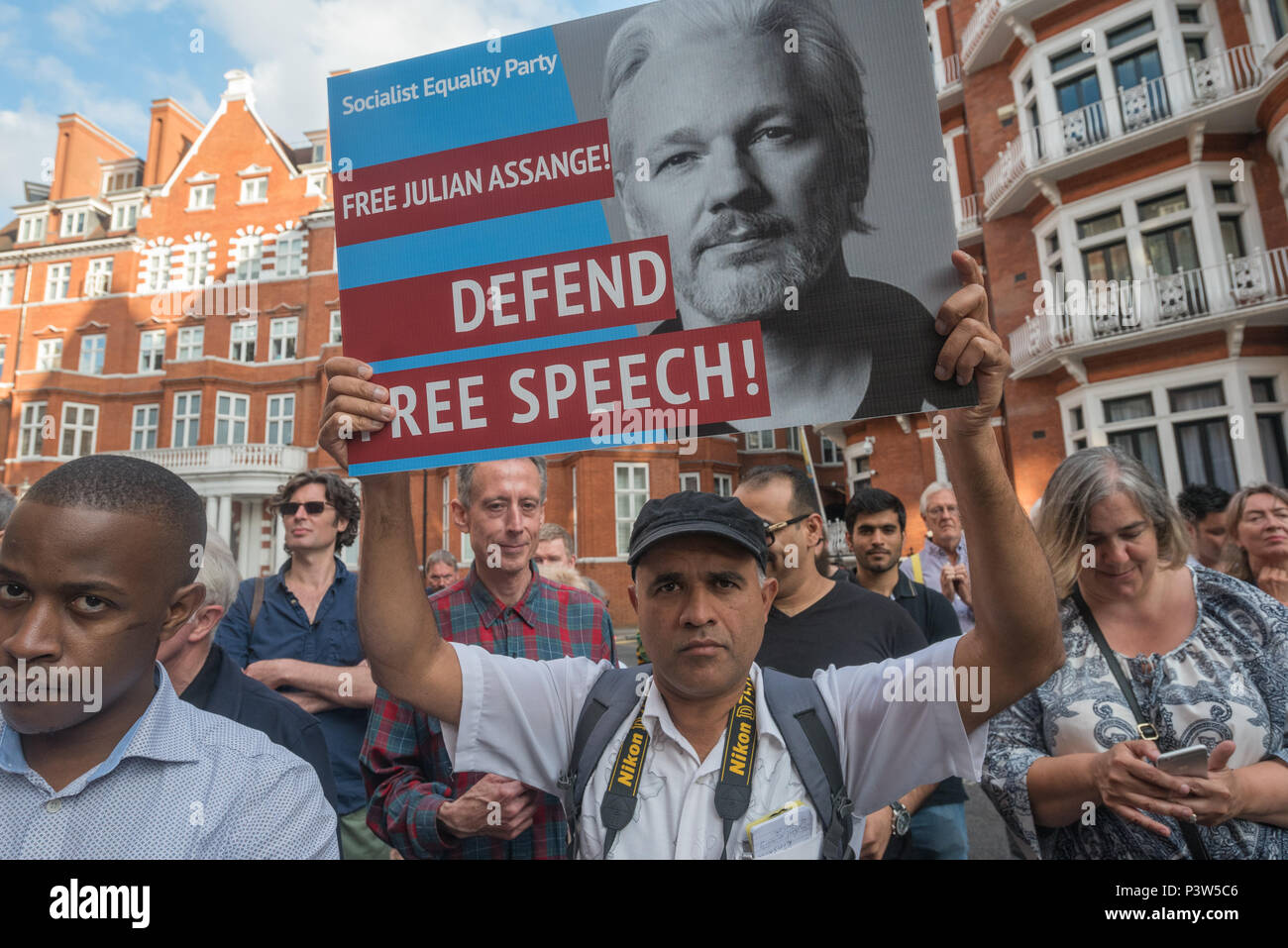 London, UK. 19th June 2018. A man stands in the crown in front of Peter Tatchell holding up a poster at the rally outside the Ecuadorian Embassy in London calling for Julian Assange to be allowed safe passage to the place of his choice to mark six years since he was given asylum there. They called for the UK authorities to allow him to leave the embassy and go to the country of his choice without being arrested. Credit: Peter Marshall/Alamy Live News - Stock Image