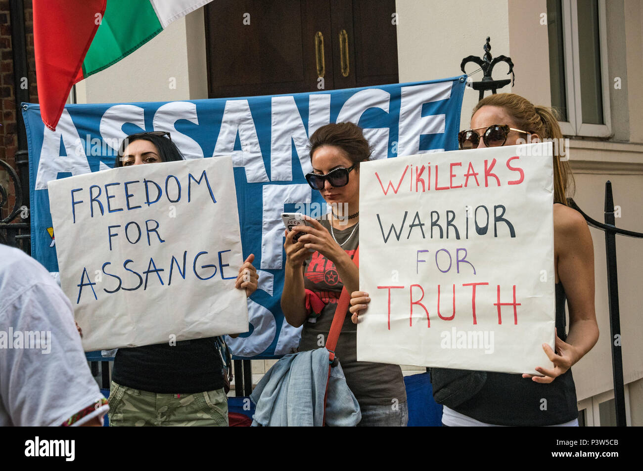 London, UK. 19th June 2018. People with posters 'Freedom for Assange' and 'Wikileaks Warrior For Truth' at the rally outside the Ecuadorian Embassy in London calling for Julian Assange to be allowed safe passage to the place of his choice to mark six years since he was given asylum there. They called for the UK authorities to allow him to leave the embassy and go to the country of his choice without being arrested. Credit: Peter Marshall/Alamy Live News - Stock Image