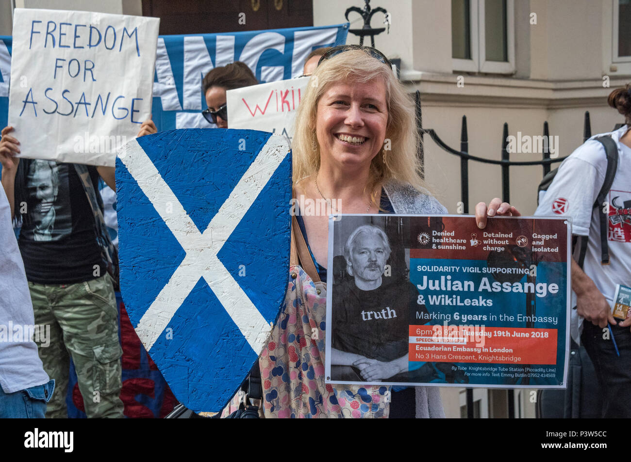 London, UK. 19th June 2018. A protester from Scotland with a saltire shield holds a poster at the rally outside the Ecuadorian Embassy in London calling for Julian Assange to be allowed safe passage to the place of his choice to mark six years since he was given asylum there. They called for the UK authorities to allow him to leave the embassy and go to the country of his choice without being arrested. Credit: Peter Marshall/Alamy Live News - Stock Image