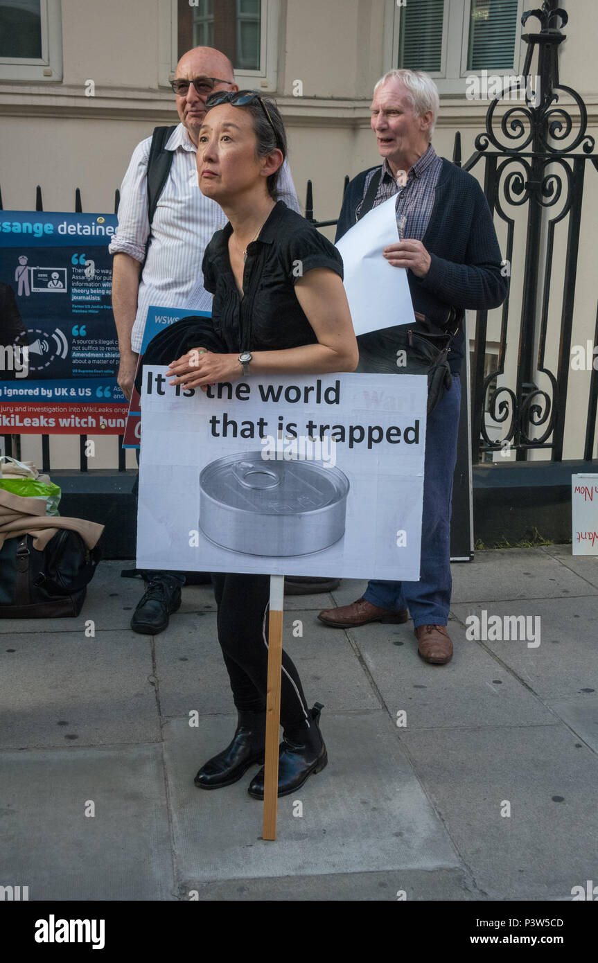 London, UK. 19th June 2018. A woman holds a poster 'It is the world that is trapped' at the rally outside the Ecuadorian Embassy in London calling for Julian Assange to be allowed safe passage to the place of his choice to mark six years since he was given asylum there. They called for the UK authorities to allow him to leave the embassy and go to the country of his choice without being arrested. Credit: Peter Marshall/Alamy Live News - Stock Image