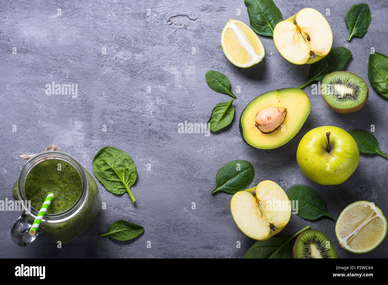 Green food background. Lime, apple, spinach, avocado and lime with smoothie in jar glass. Superfoods, detox, diet, healthy food - Stock Image