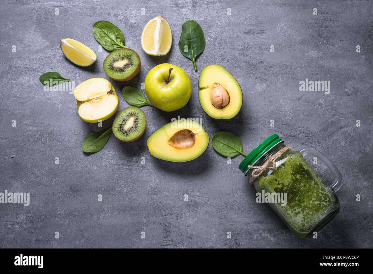 Green smoothie in mason jar and ingredients. Superfoods, detox, diet, healthy food. Lime, apple, spinach avocado and lime - Stock Image