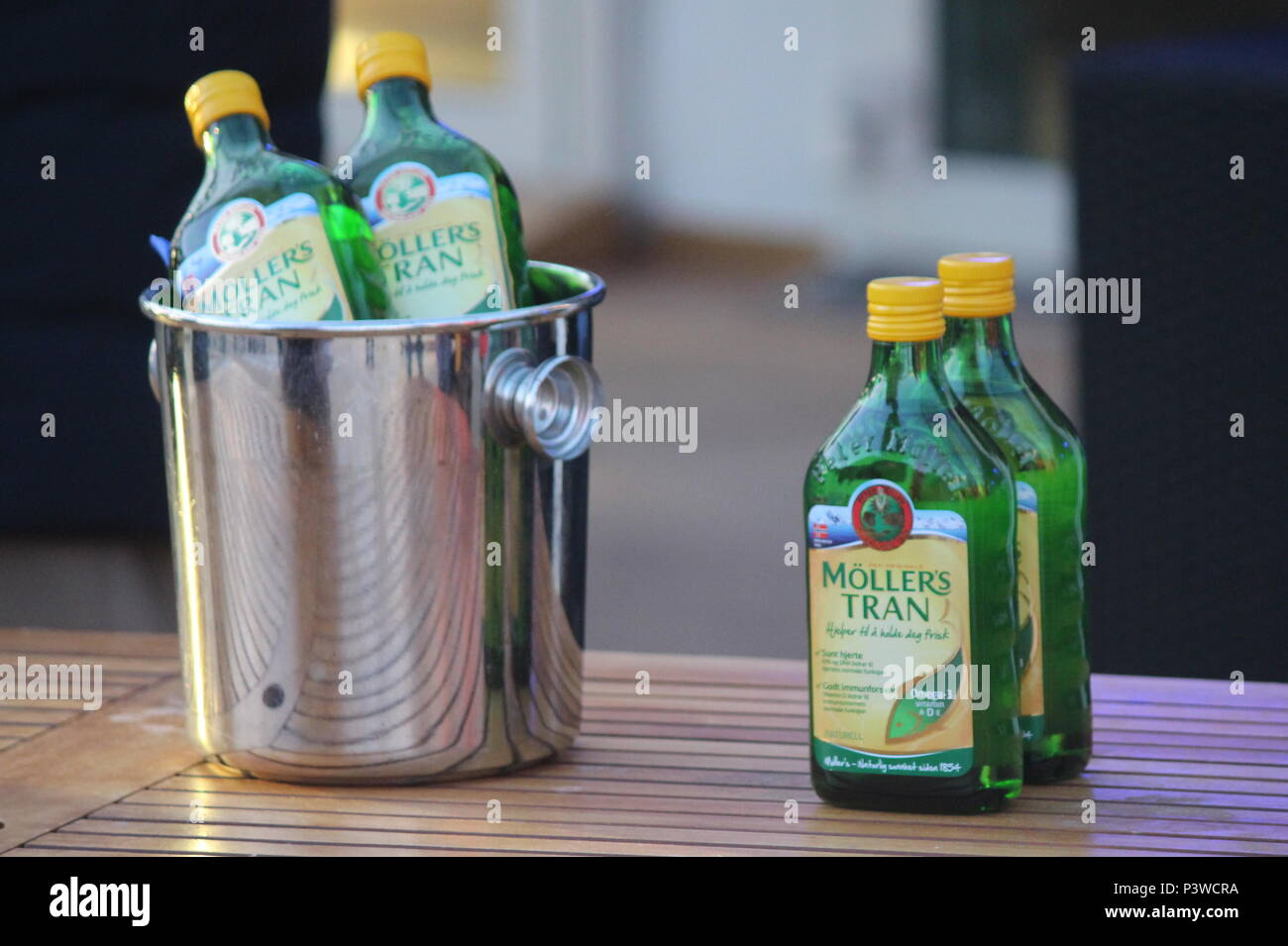 Four bottles of Moller's Tran Cod liver oil, tow on table and two in stainless steel ice bucket taken on Hurtigruten cruise crossing the Artic circle Stock Photo
