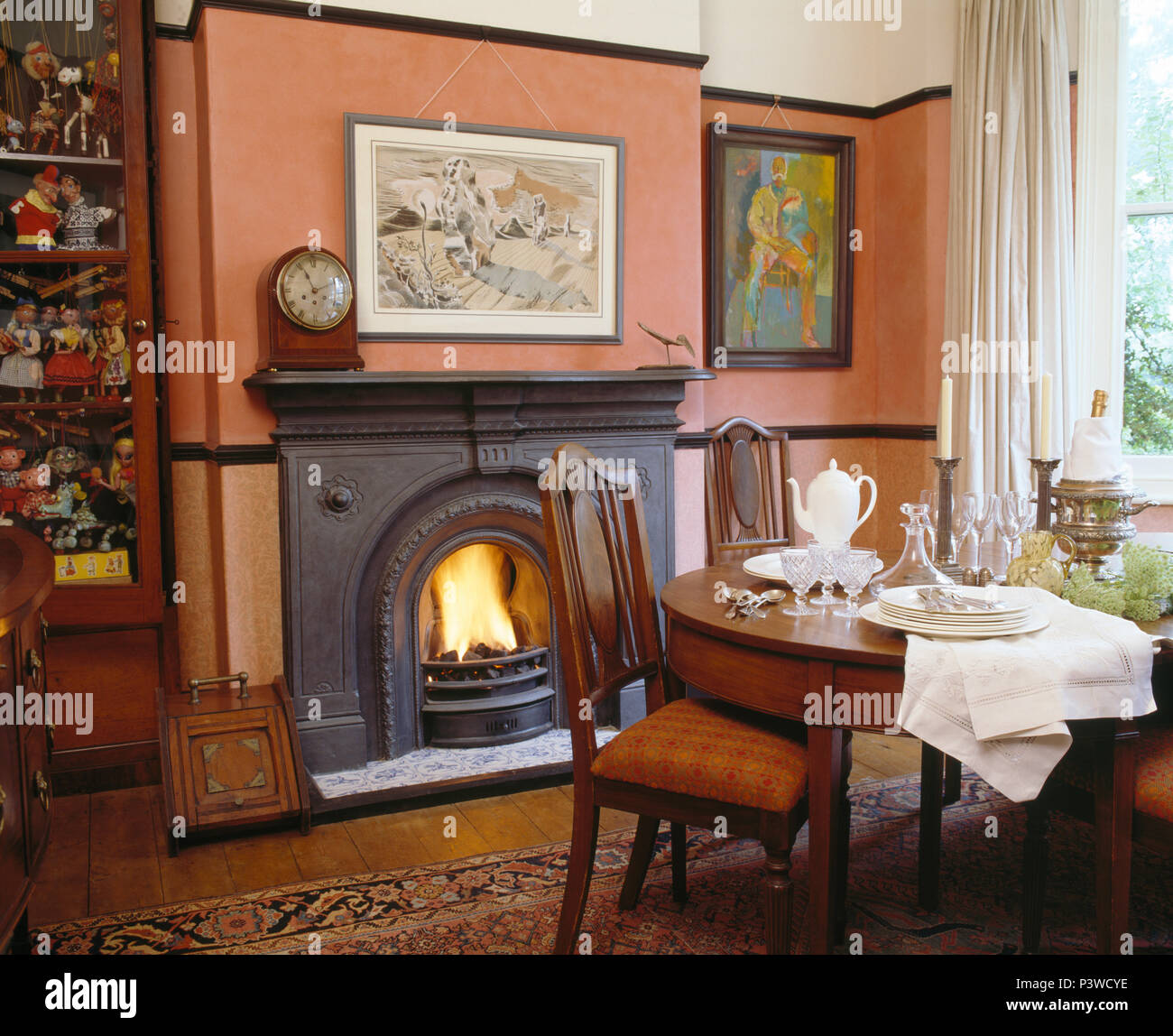 Genial Antique Table And Chairs In Pale Terracotta Victorian Style Dining Room  With Lighted Fire In Fireplace