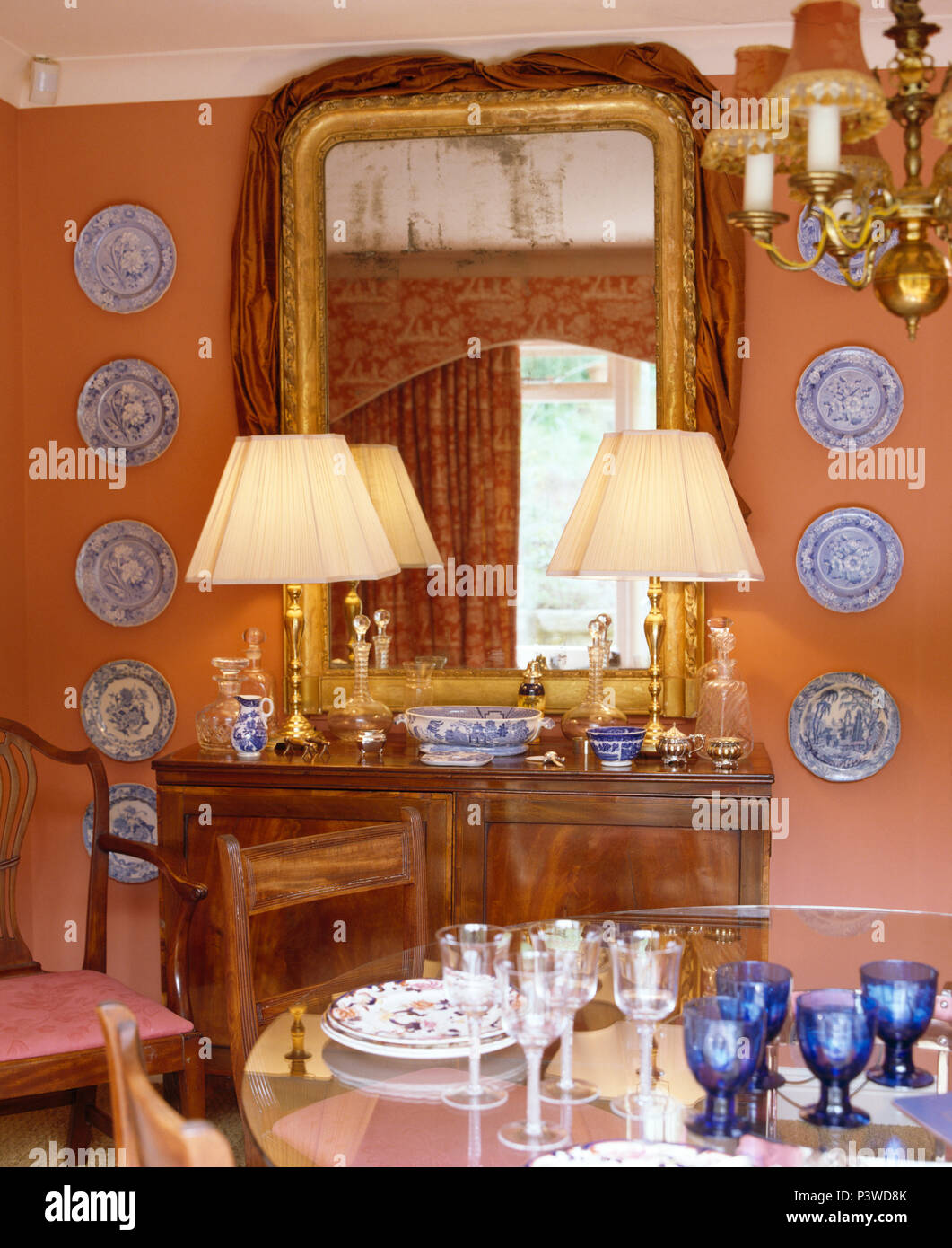 Collection of blue+white plates on either side of antique mirror on cupboard with lighted lamps in peach dining room - Stock Image