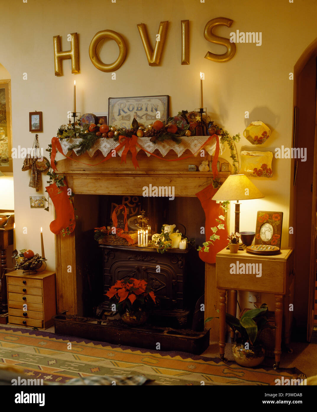 Gold Hovis' letters above fireplace with cast iron stove in dining room decorated for Christmas - Stock Image