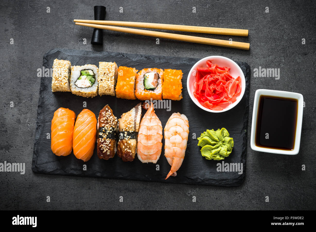 Sushi and sushi roll set on black stone table top view. Traditional asian food. - Stock Image