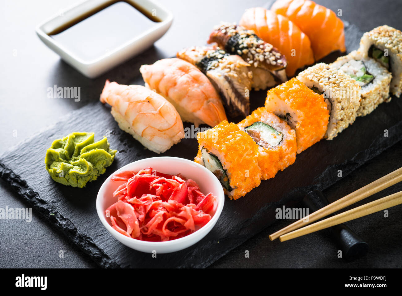 Sushi and sushi roll set on black stone table. Traditional asian food. - Stock Image