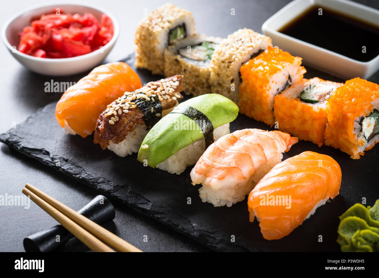 Sushi and sushi roll set on black stone table. Traditional asian food. Close up. - Stock Image
