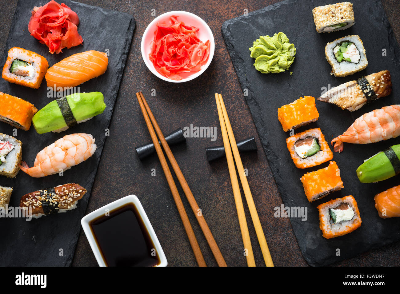Sushi, maki, nigiri and sushi roll set on dark stone table top view. Japanese food. - Stock Image