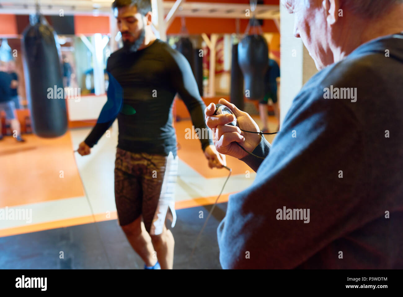 Trainer setting timer for man warming up - Stock Image