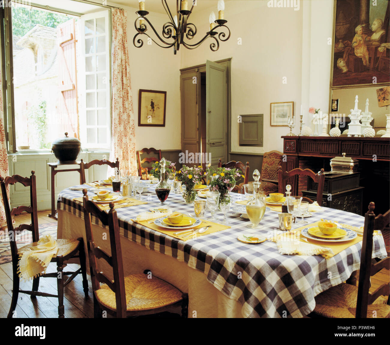 Yellow Crockery On Blue+white Checked Tablecloth In French Country Dining  Room With Ladder Back Rush Seated Chairs
