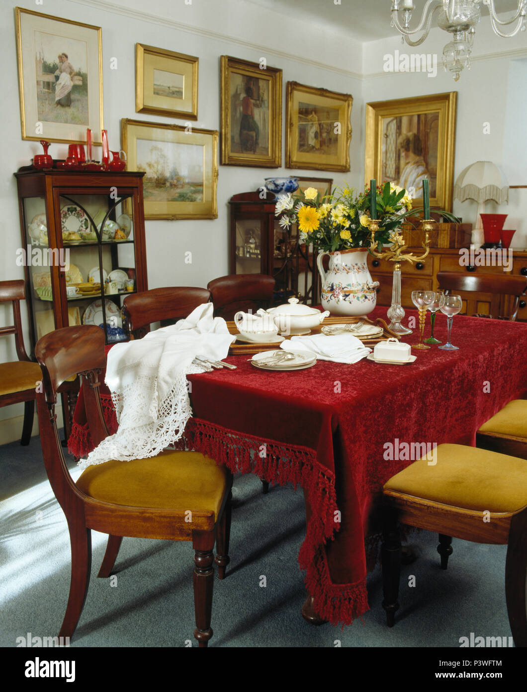 Table With Red Velour Cloth And Antique Chairs With Mustard Yellow  Upholstered Seats In Edwardian Style Dining Room