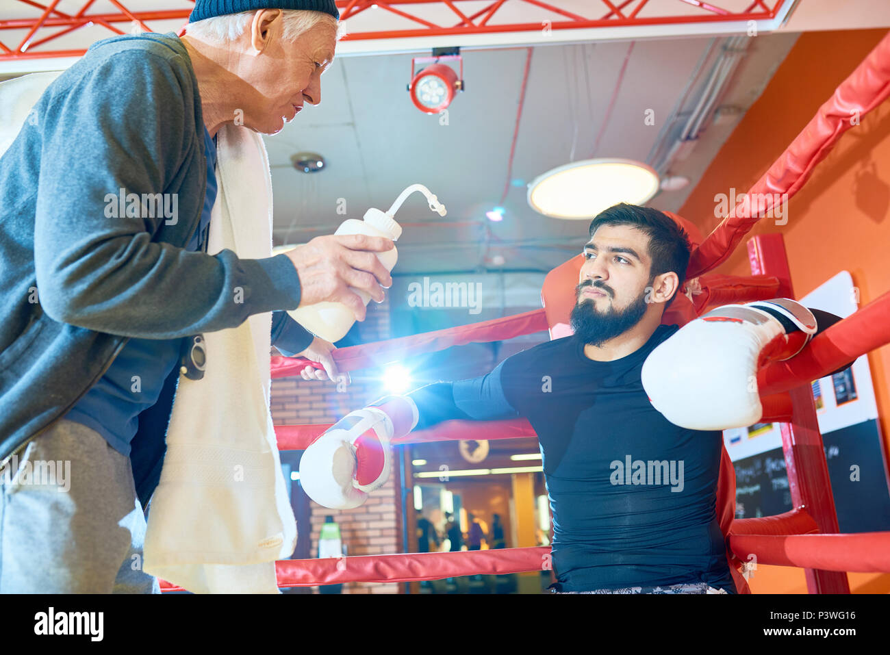 Serious man boxing with trainer Stock Photo